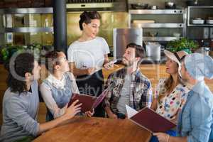 Waitress talking to customers in restaurant