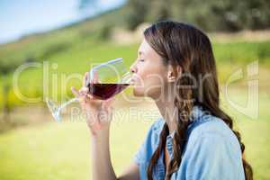 Side view of woman drinking red wine