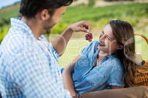 Man feeding grapes to cheerful partner