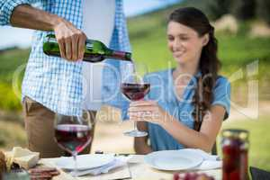 Man pouring red wine in glass held by woman