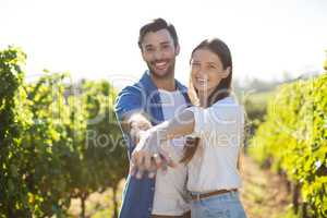 Portrait of smiling young couple holding hands at vineyard
