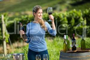 Smiling woman holding wineglass and bottle at vineyard