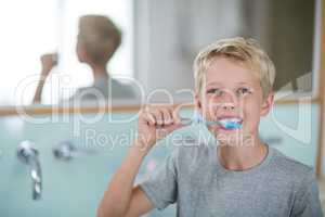 Portrait of boy brushing his teeth in bathroom