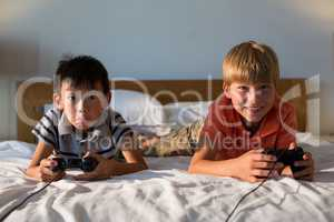 Siblings playing video game on bed