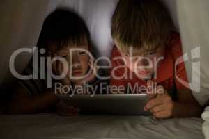 Siblings under bed sheet using digital tablet on bed