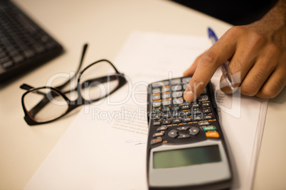 Cropped hand on business person using calculator by eyeglasses at office