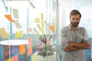 Portrait of confident businessman with arms crossed standing by strategy on glass at office