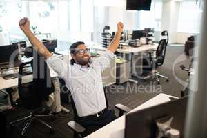 Happy businessman with arms raised in office