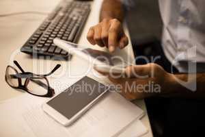 Businessman using digital tablet while sitting in office