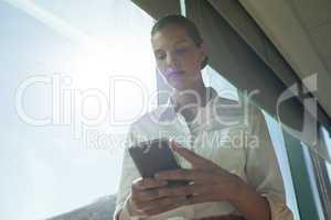 Businesswoman using mobile phone in office on sunny day