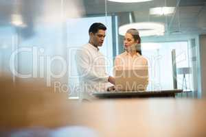 Young business people discussing over laptop in office