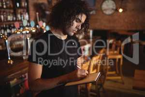Young barman writing on diary