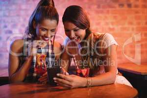 Two young women using mobile phone