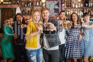 Cheerful friends holding beer glasses in pub