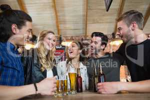 Happy friends standing by beer glass and bottles on table