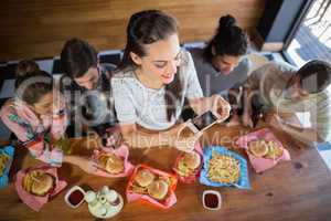 Woman with friends photographing food in restaurant