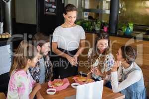 Waitress standing by customers in +restaurant