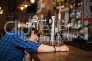 Man leaning on counter in pub