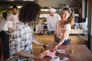 Waitress serving burger to young man in restaurant