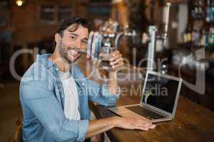 Young man holding beer while sitting by laptop in pub