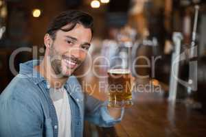 Portrait of man holding beer glass at pub