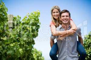 Happy couple piggybacking at vineyard against blue sky
