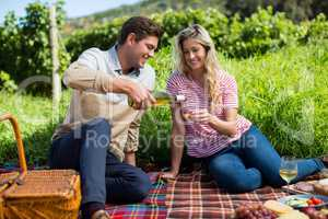 Happy man pouring wine in glass held by woman