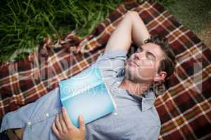 Man with book sleeping on blanket