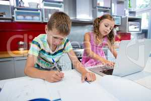 Boy doing his homework while girl using laptop in kitchen
