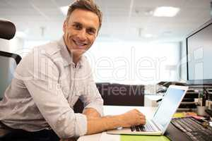 Portrait of smiling businessman using laptop while sitting in office