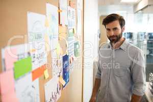 Portrait of businessman standing by soft board