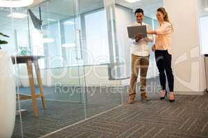 Confident business people using laptop in modern office