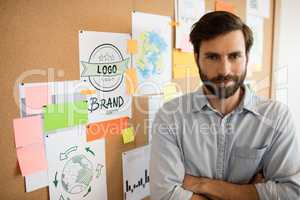 Businessman with arms crossed standing by soft board