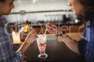 Couple having milkshake at counter