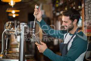 Happy bartender pouring beer from tap