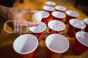 Cropped hand of man playing beer pong
