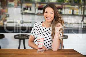 Portrait of smiling woman sitting by drink on table