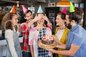 Happy friends giving suprise to woman during her birthday