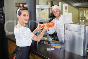 Chef giving burgers to waitress in commercial kitchen