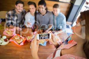 Young woman photographing friends in restaurant