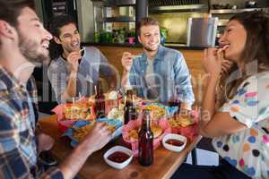 Cheerful friends eating French fries in restaurant