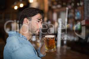 Man looking away while drink beer at pub