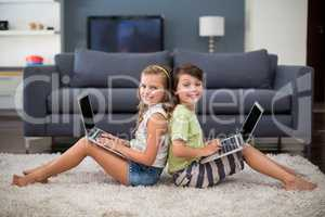 Smiling siblings sitting back to back and using laptop in living room