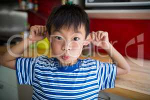 Boy making funny face in kitchen