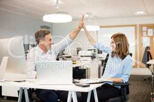 Happy business colleagues giving high five to each other