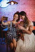 Young women taking a selfie while having cocktail drinks