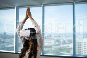 Businesswoman practicing yoga with arms raised while using virtual reality glasses