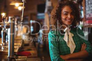 Portrait of waitress standing with arms crossed at counter