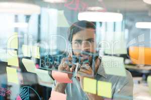 Businessman using mobile phone while looking at plans written on glass