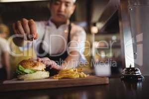 Chef placing tooth pick over burger at order station